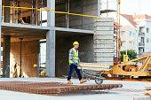 Worker pushing wheelbarrow on construction site