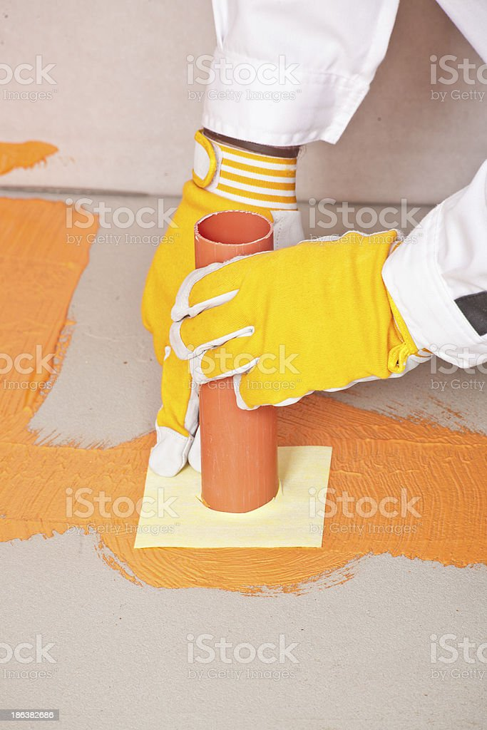 worker puts a waterproof gasket around the pipe royalty-free stock photo