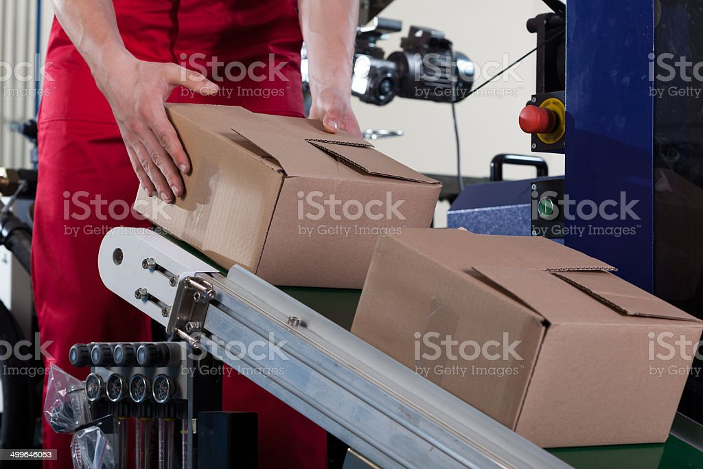 Worker putting a box on conveyor belt stock photo