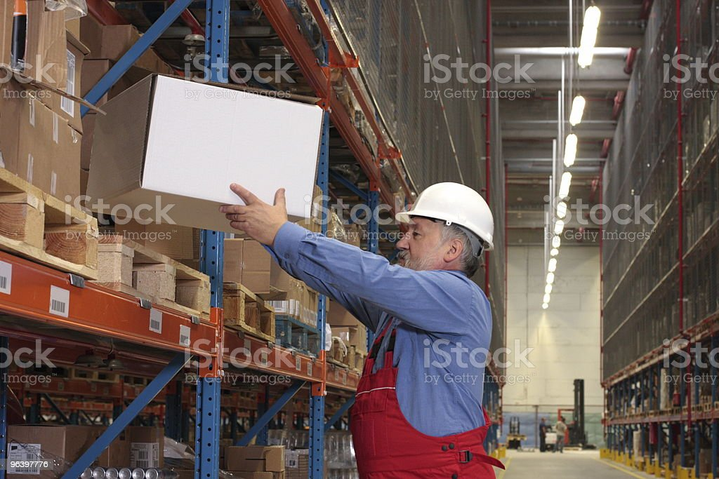 worker  putting box on  shelf in warehouse stock photo