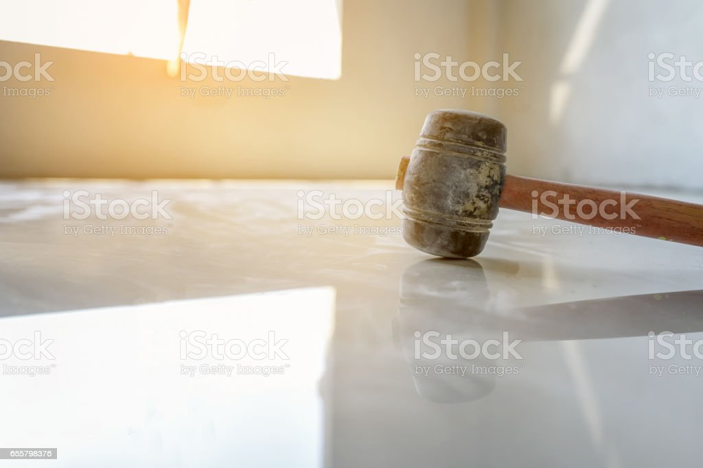 worker putting ceramist tile on the floor. Professional ceramist is laying ceramic tile on the floor stock photo
