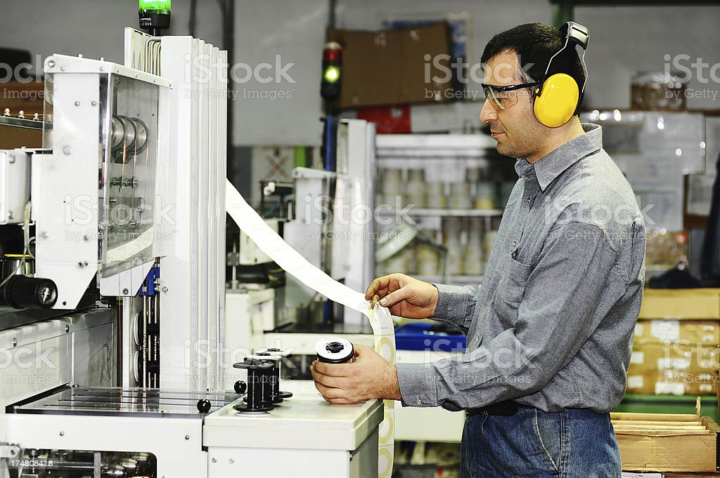 Worker putting labels on new products stock photo