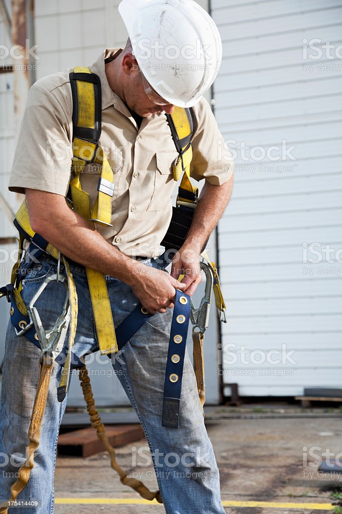 Worker putting on safety harness royalty-free stock photo