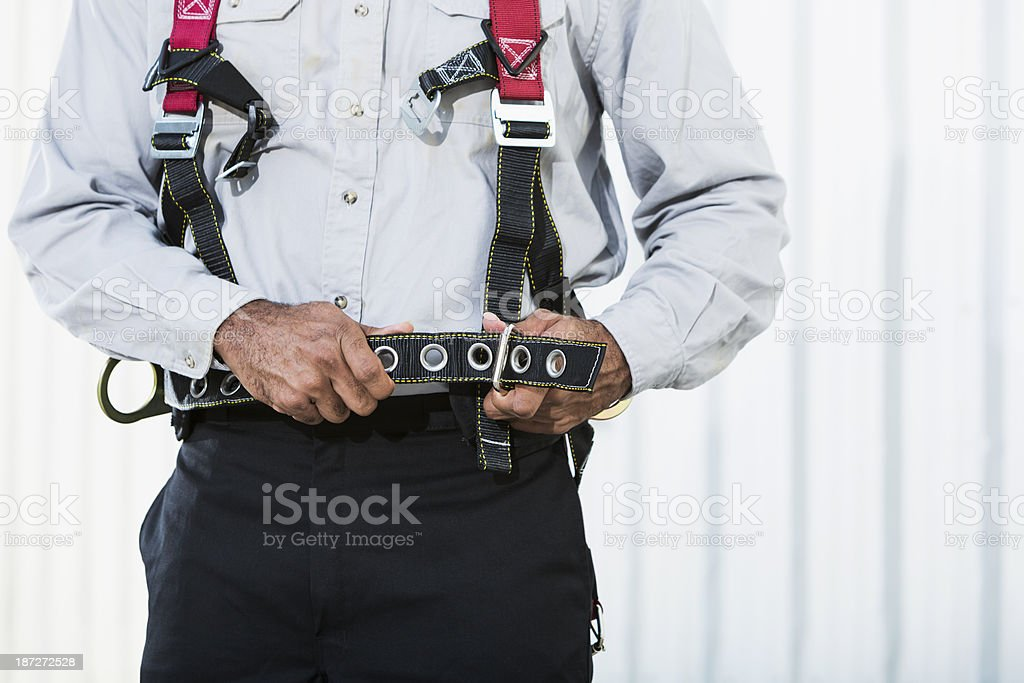 Worker putting on safety harness stock photo