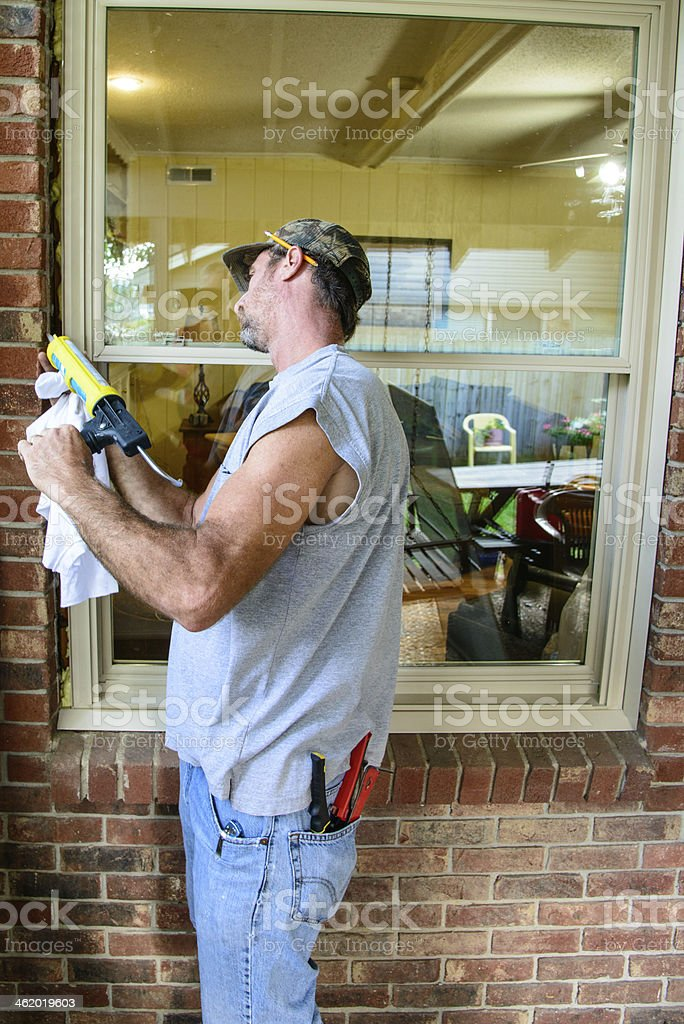 Worker putting silicone around window stock photo
