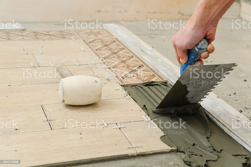 Worker putting tiles on the floor. royalty-free stock photo