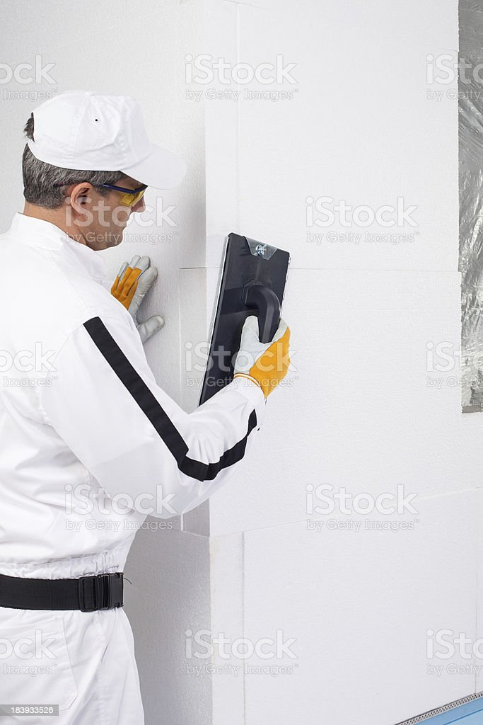 Worker rasping the corners of insulation panels royalty-free stock photo
