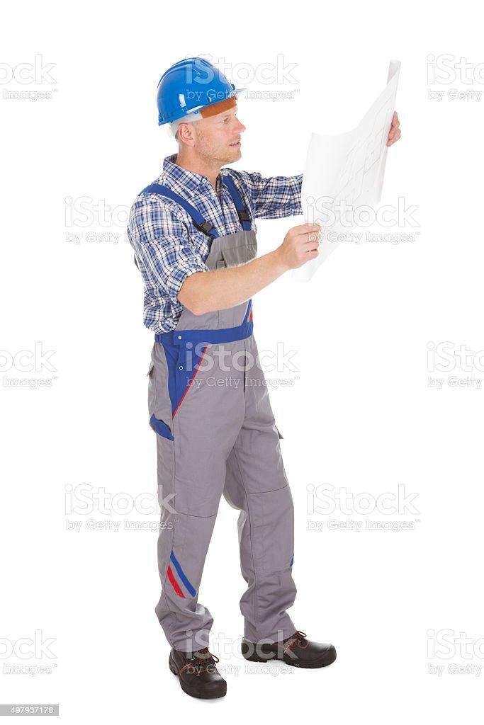 Worker Reading Blueprint Over White Background stock photo