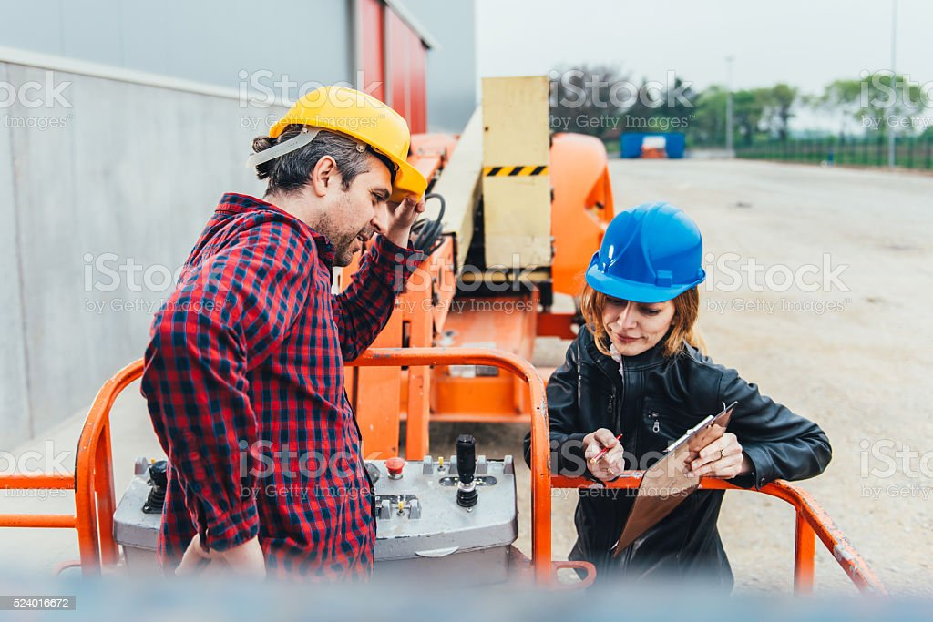 Worker receiving instruction about Straight Boom Lift stock photo
