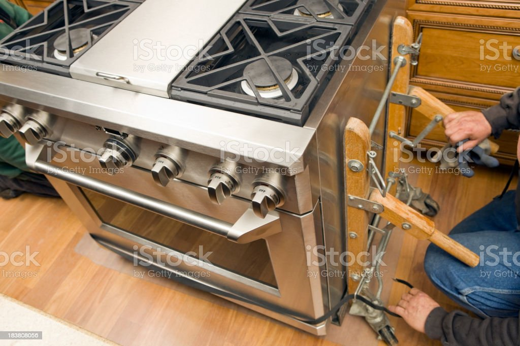 Worker Removes Appliance Dolly from New Kitchen Range royalty-free stock photo