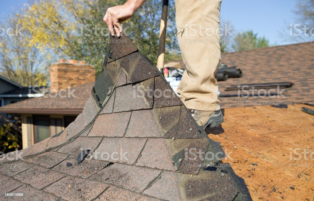 Worker Removing Old Roof Shingles for Replacement stock photo