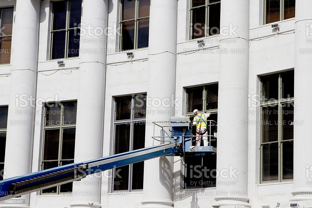 Worker Renovating Denver City and County Building stock photo