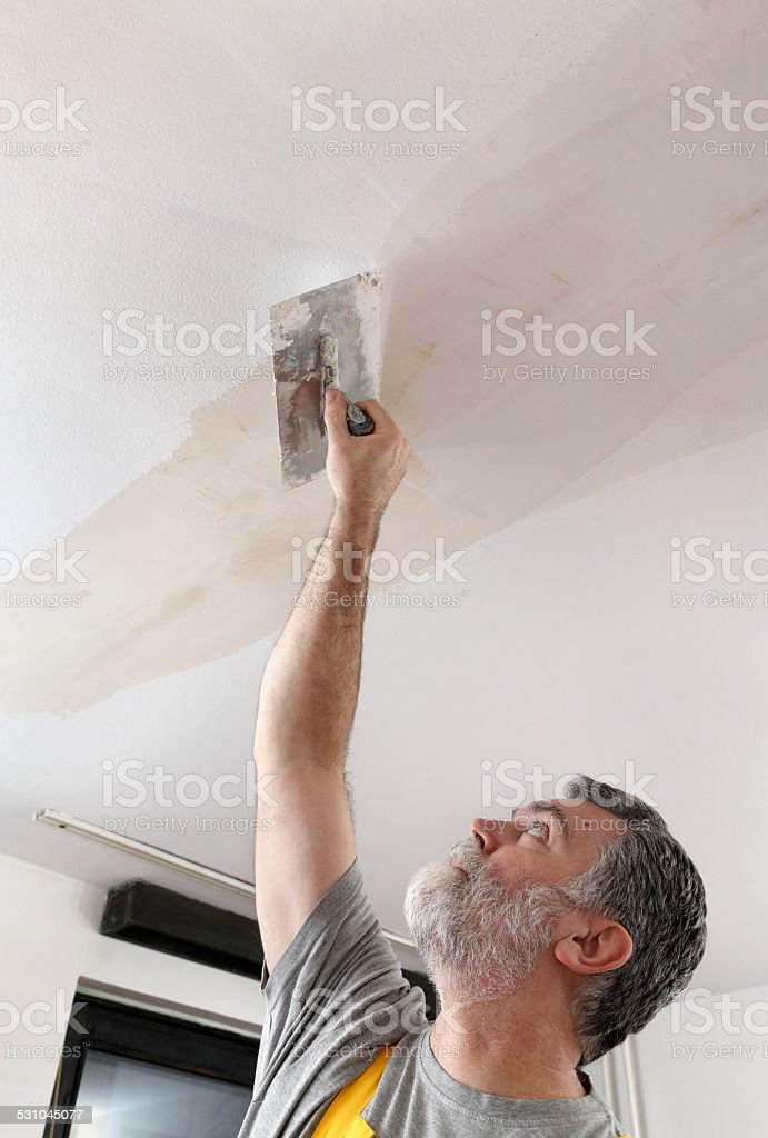 Worker repairing plaster at ceiling stock photo