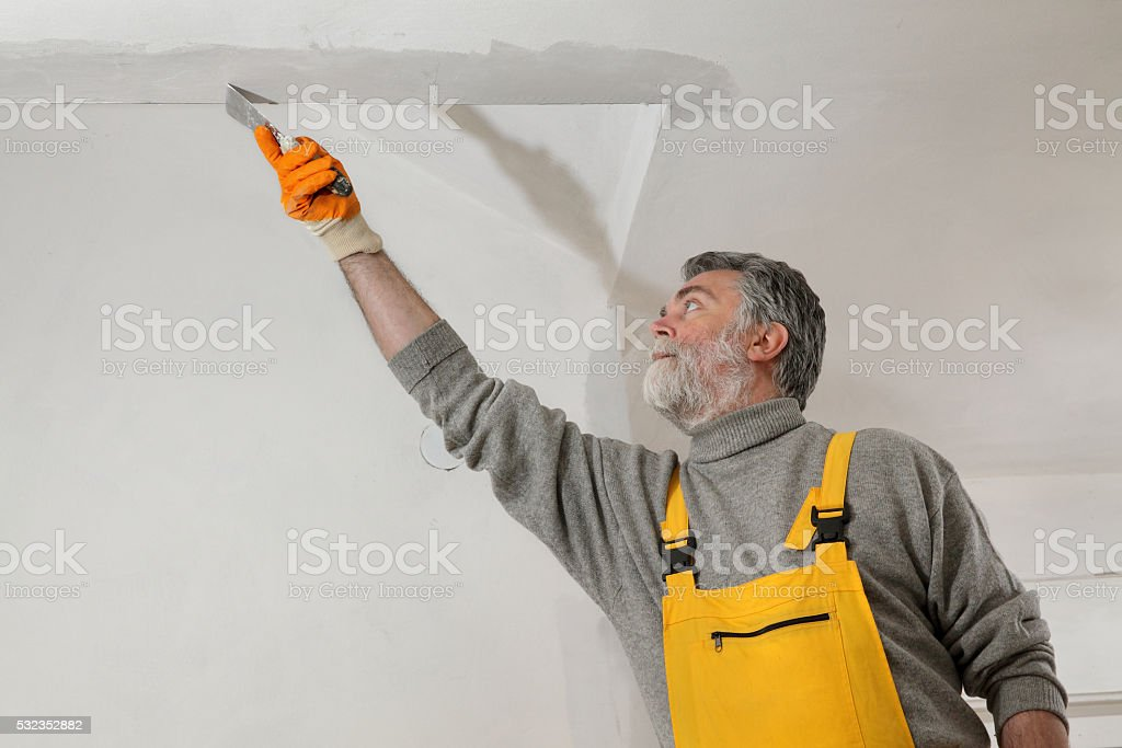 Worker repairing plaster at ceiling stock photo