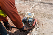 Worker reversible plate compactor on a roadwork site.