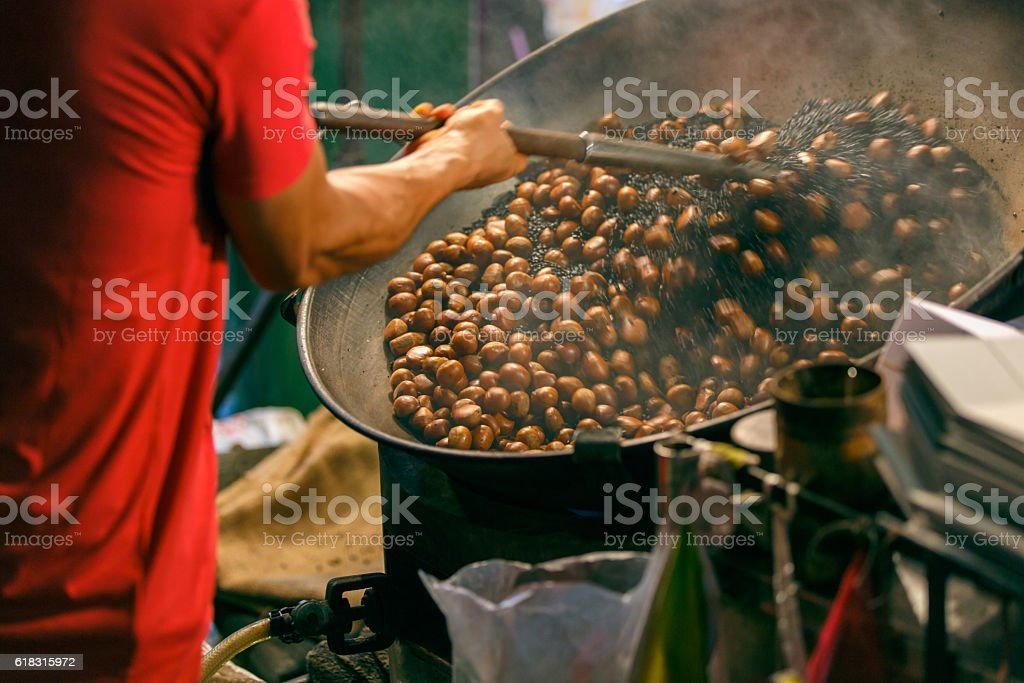 Worker roasting chestnuts in street chinatown stock photo