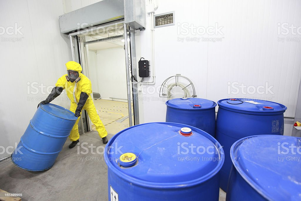 Worker rolling the barrel with toxic substance royalty-free stock photo