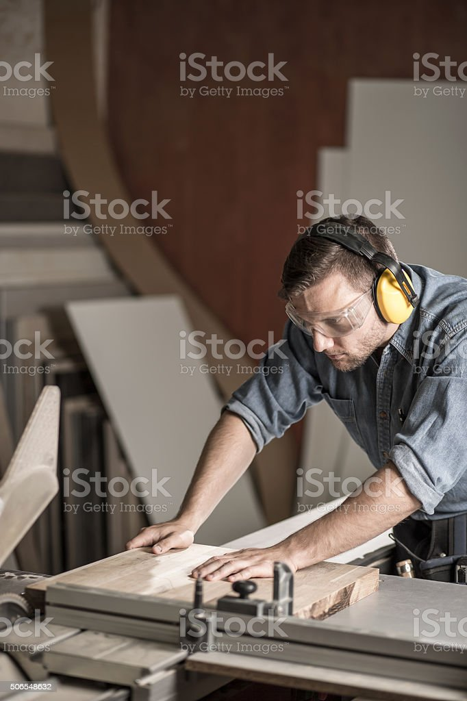 Worker sawing board for furniture stock photo
