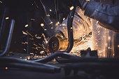 Worker sawing metal with disk grinder generating sparks