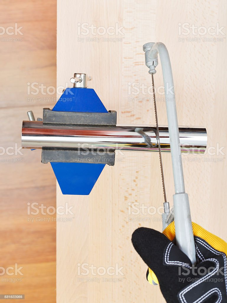 worker saws metal drain pipe gripped in vice stock photo