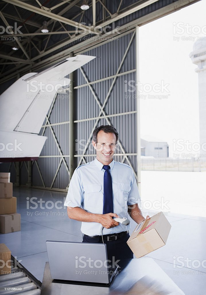 Worker scanning box in hangar royalty-free stock photo