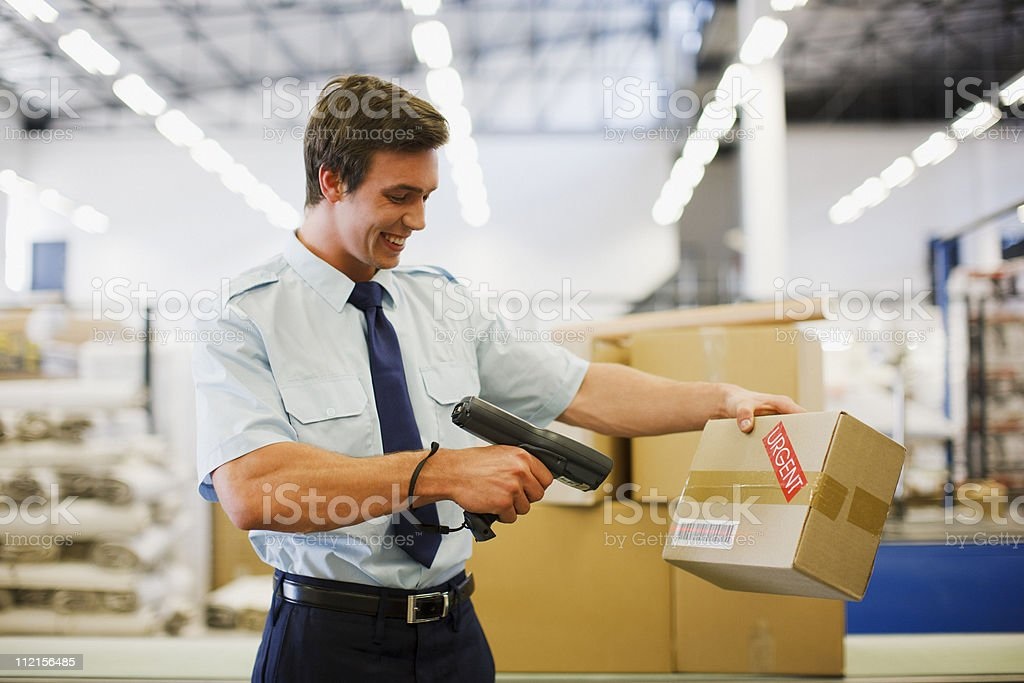 Worker scanning box in shipping area stock photo