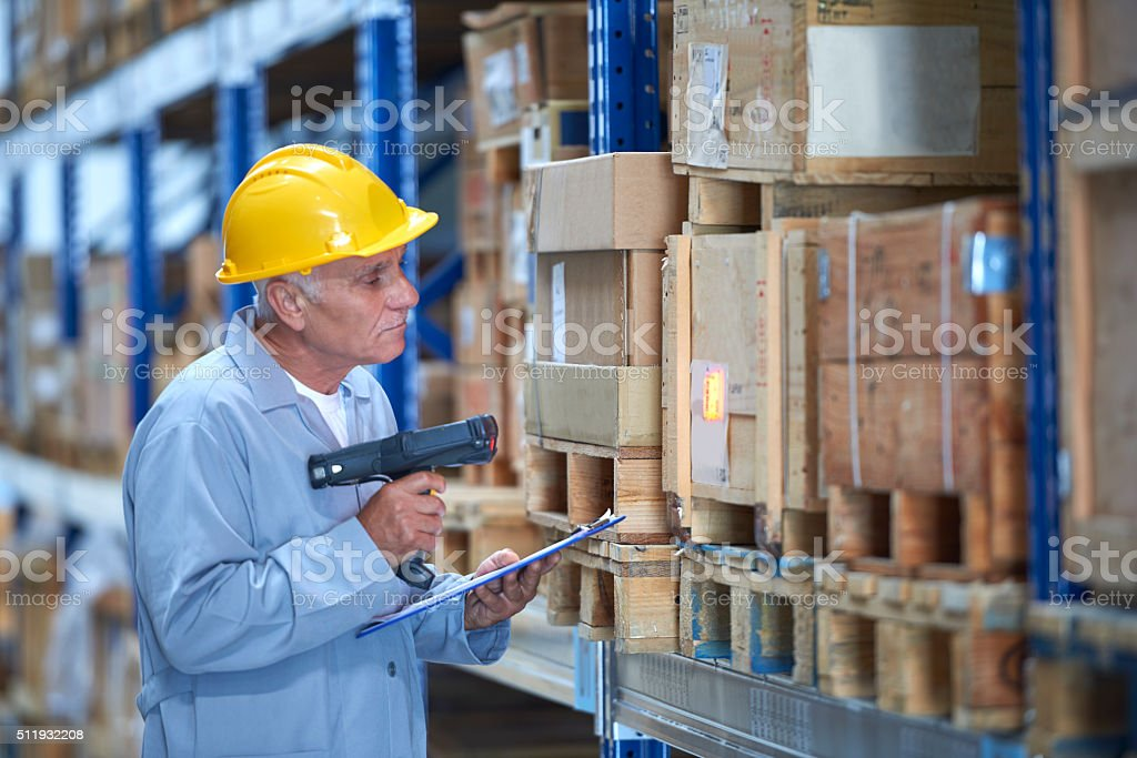 Worker scanning inventory in warehouse stock photo