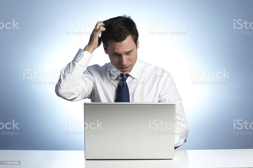 IT Worker Scratches Head while viewing Laptop Computer royalty-free stock photo