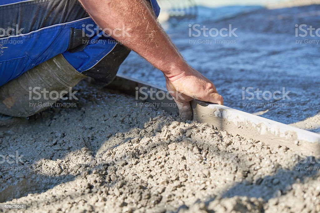 Worker screeding cement floor with screed stock photo