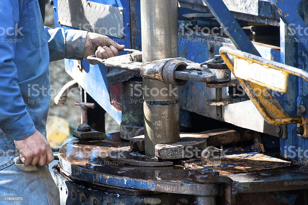 Worker screwing on a drill casing stock photo