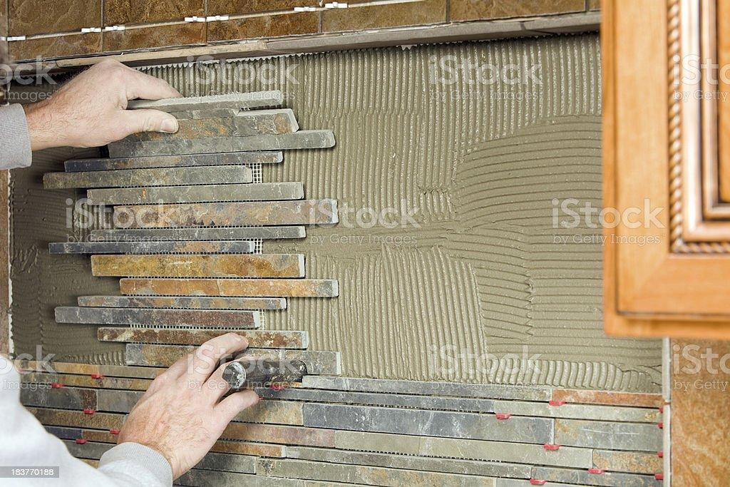 Worker Setting a New Kitchen Backsplash Stone stock photo