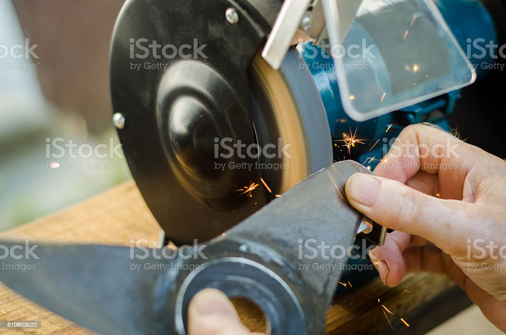 Worker sharpening his blade lawn mower. stock photo