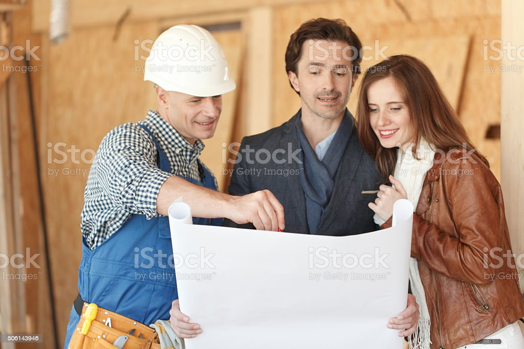 Worker shows house design plans stock photo