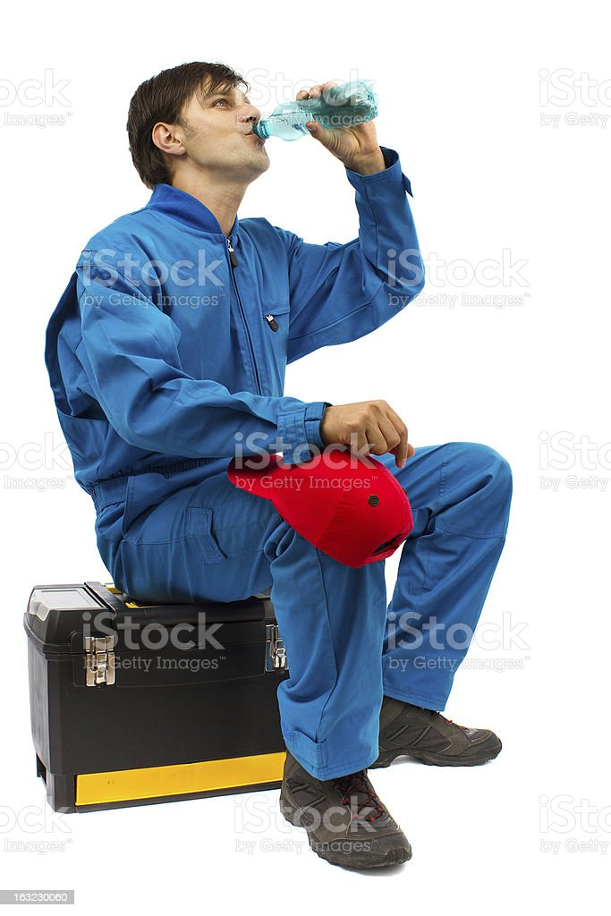 worker sitting on the toolbox drinking water royalty-free stock photo