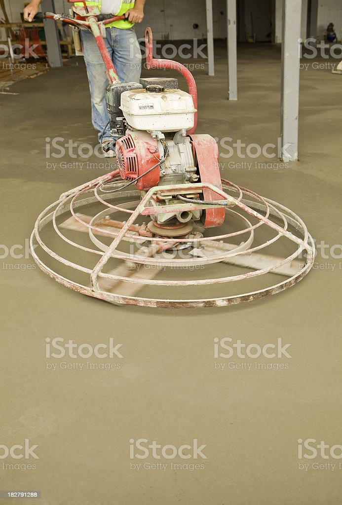 Worker Smoothing Concrete with a Power Trowel royalty-free stock photo