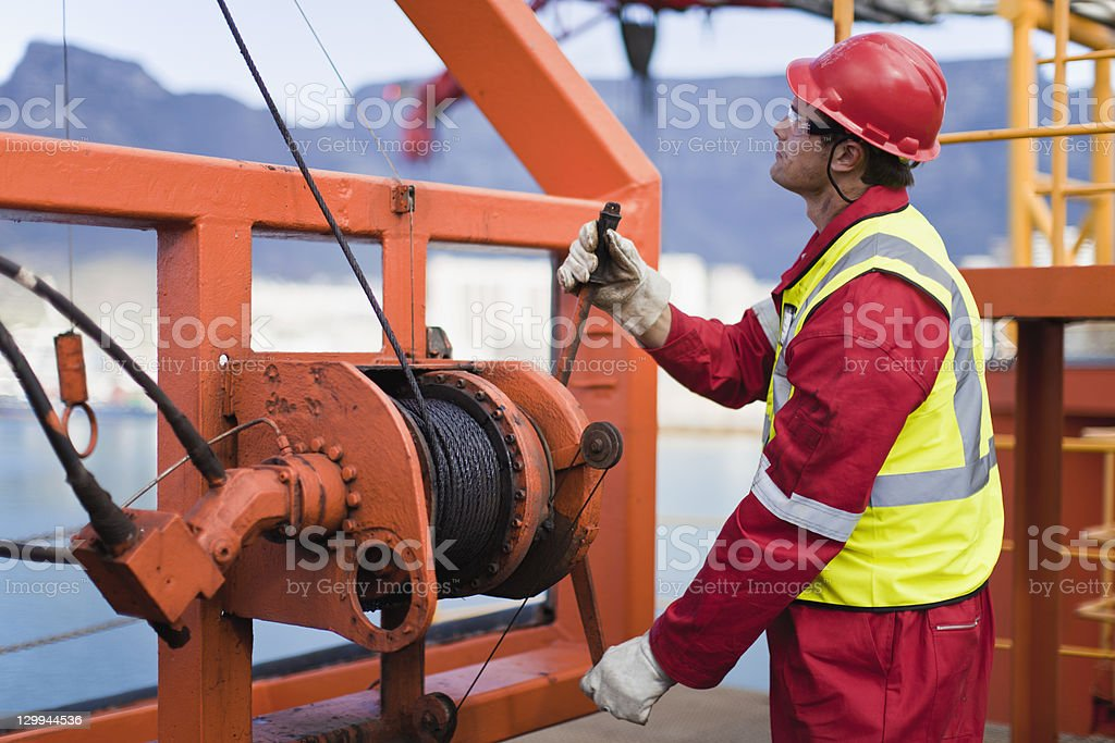 Worker spooling cord on oil rig stock photo