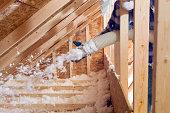 Worker Spraying Blown Fiberglass Insulation between Attic Trusse