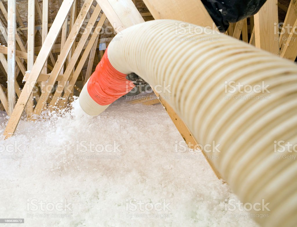 Worker Spraying Blown Fiberglass Insulation between Attic Trusses stock photo