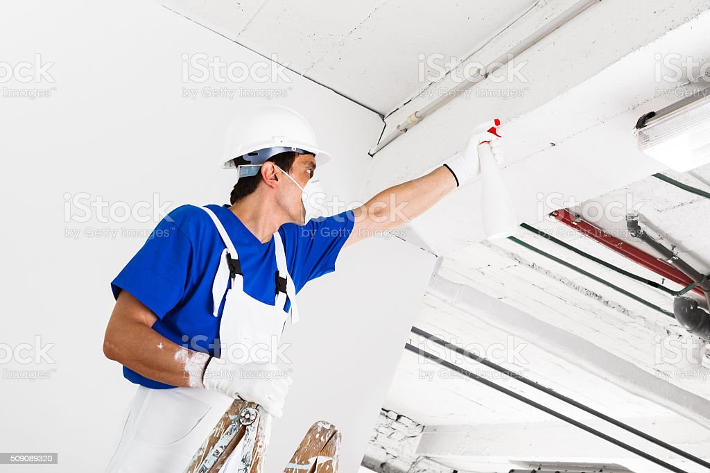 worker spraying ceiling with spray bottle stock photo