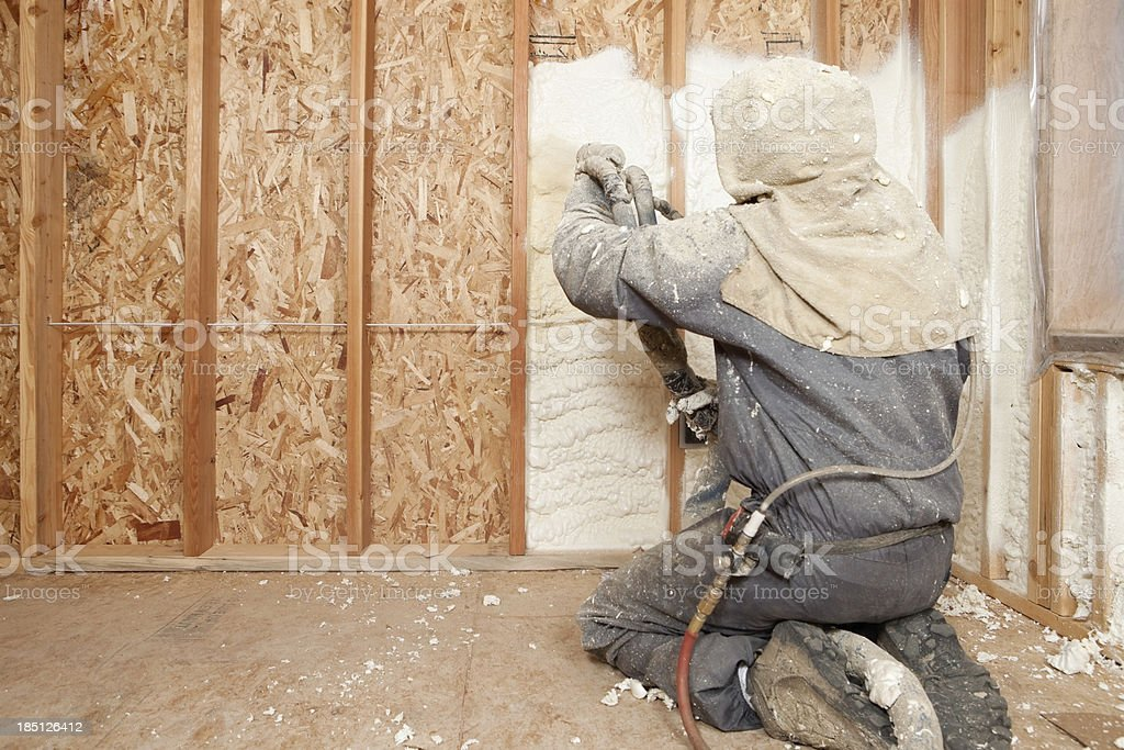 Worker Spraying Expandable Foam Insulation between Wall Studs stock photo