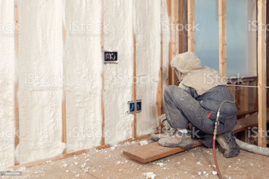 Worker Spraying Expandable Foam Insulation between Wall Studs royalty-free stock photo