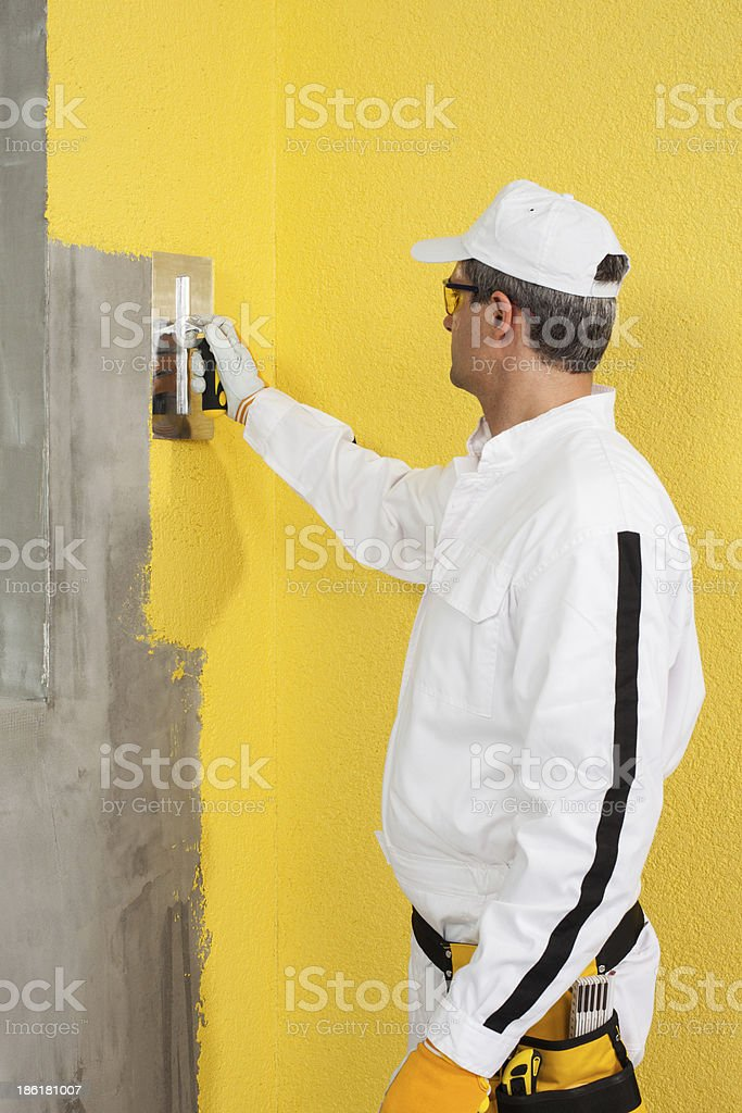 Worker spreading plaster on a corner-wall royalty-free stock photo