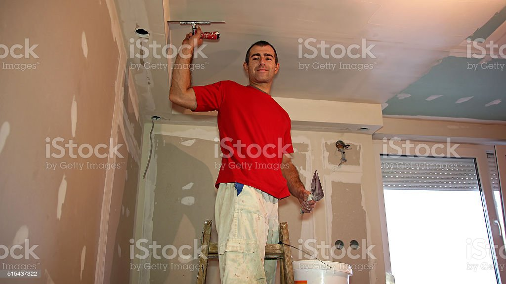 Worker Spreading Plaster with Trowel to Gypsum Board stock photo