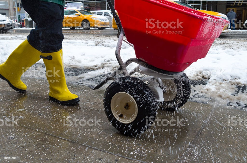 Worker spreading salt on icy sidewalk stock photo
