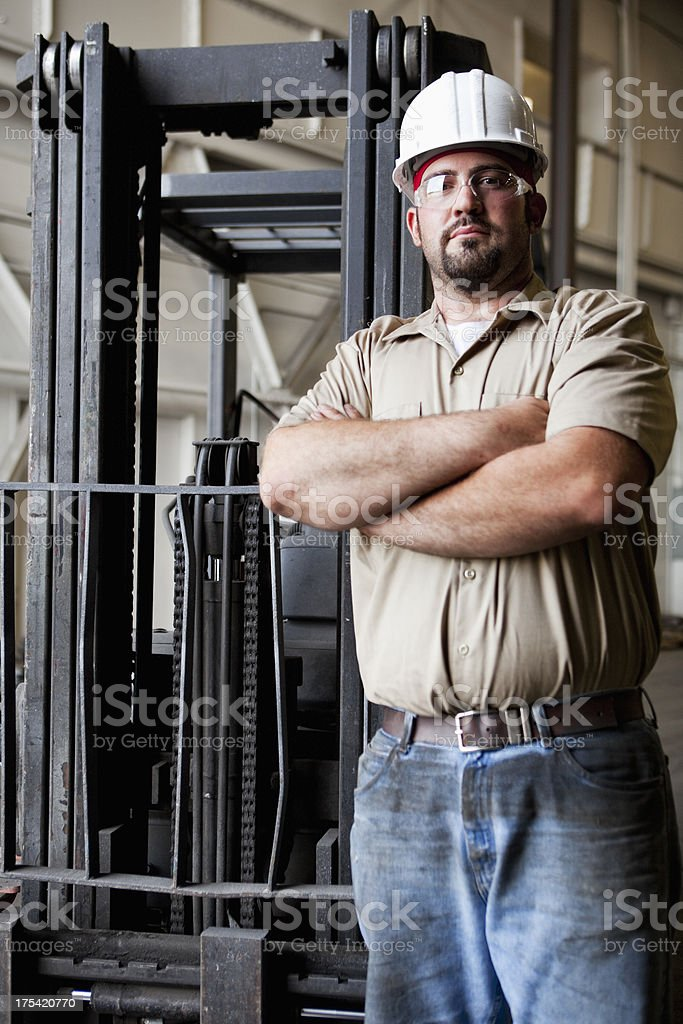 Worker standing in front of forklift stock photo