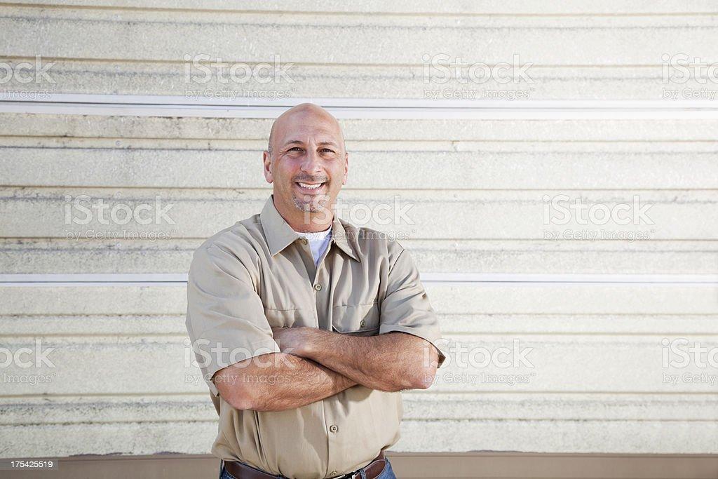 Worker standing in front of warehouse door stock photo