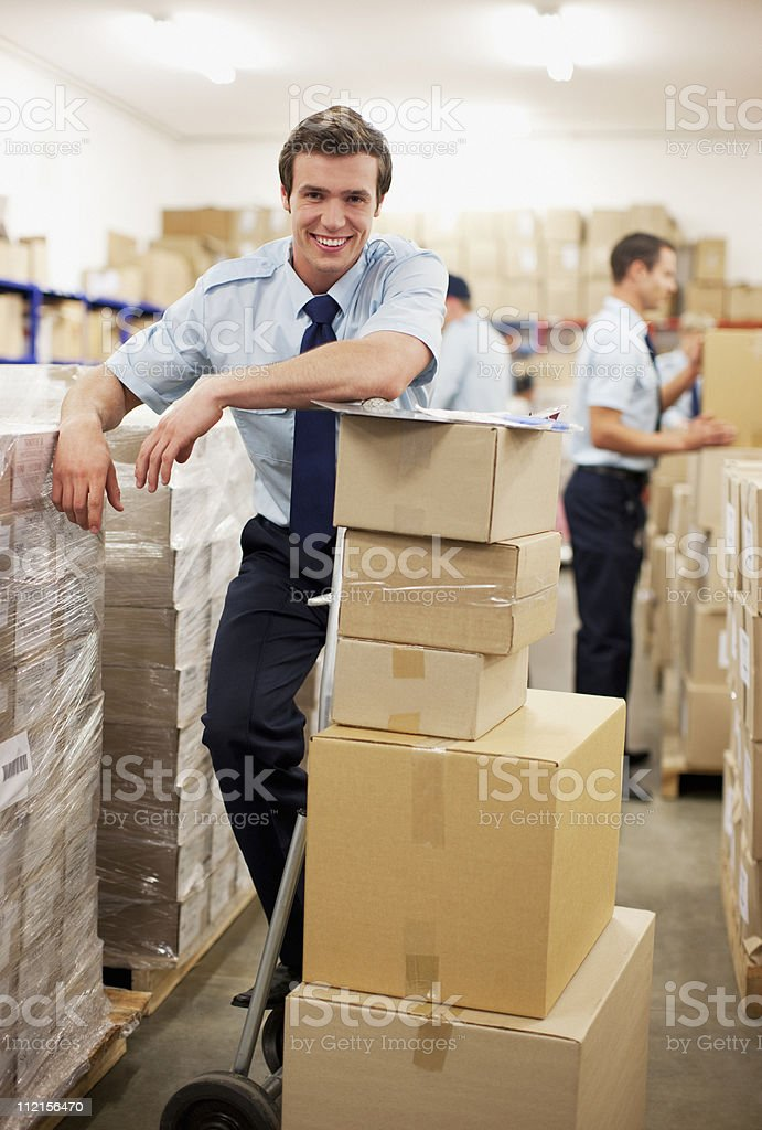 Worker standing near boxes in shipping area royalty-free stock photo