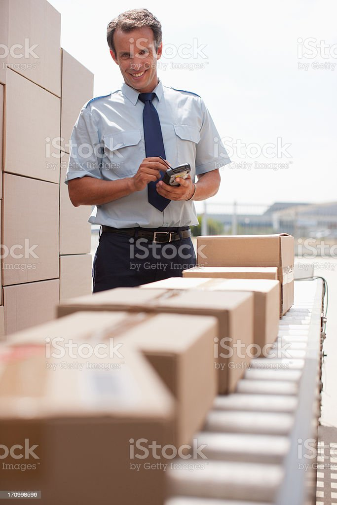 Worker standing near boxes on conveyor belt stock photo