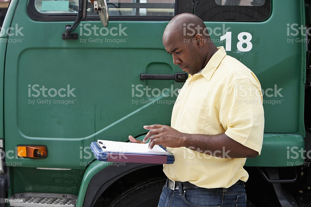 Worker standing next to truck stock photo