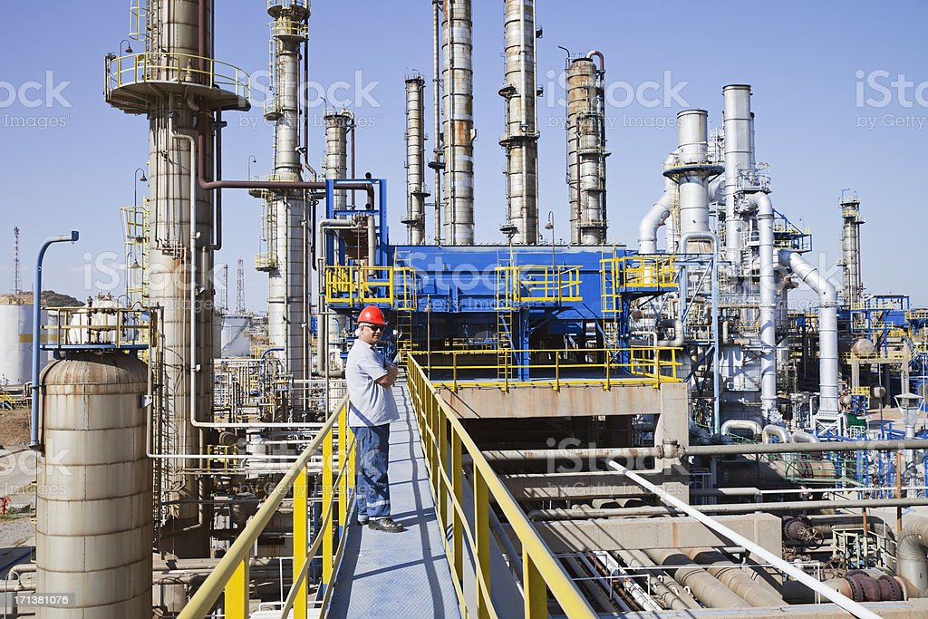 Worker standing on deck of petrochemical plant stock photo